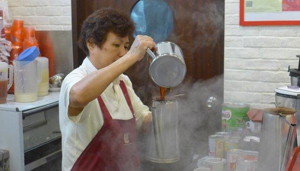 Ya Kun worker making coffee