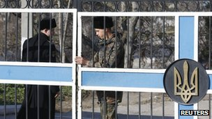 A member of the Russian navy (L) stands next to a Ukrainian soldier closing a gate bearing the Ukrainian national coat of arms on a Ukrainian naval base in Sevastopol 21 March 2014