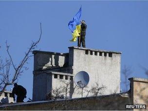 A Ukrainian soldier raises a Ukrainian flag over their base in the Crimean port of Sevastopol on 21 March 2014.