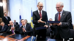 European Council president Herman Van Rompuy (R) exchanges documents with Ukrainian Prime Minister Arseniy Yatsenyuk during the signing of the political provisions of the Association Agreement with Ukraine at the EU headquarters in Brussels on 21 March 2014