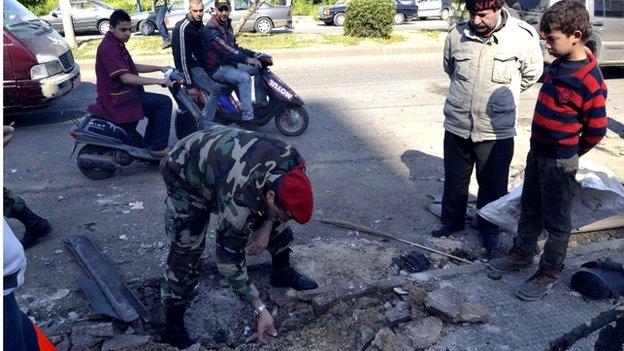Lebanese soldier inspects site of roadside bomb in Tripoli (21/03/14)