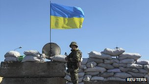 A Ukrainian soldier stands guard at a checkpoint near the town of Armyansk