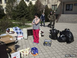 Family of Ukrainian servicemen wait near their belongings as they leave their base in the village of Lyubimovka near Sevastopol on 21 March 2014.