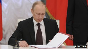 Russian President Vladimir Putin prepares to sign a law on ratification of a treaty making Crimea part of Russia, during a ceremony in Moscow's Kremlin in Moscow 21 March 2014.