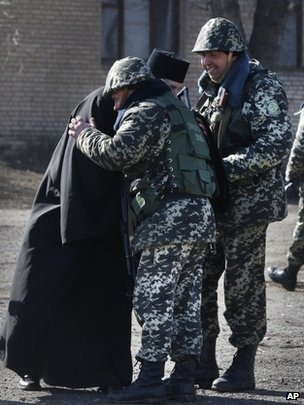 A priest blesses Ukrainian border guards at a military camp in the village of Alekseyevka on the Ukrainian-Russian border, eastern Ukraine, on 21 March 2014.