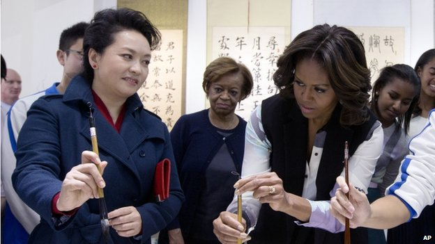 Peng Liyuan, wife of Chinese President Xi Jinping, left, shows US First Lady Michelle Obama, centre, how to hold a writing brush as they visit a Chinese traditional calligraphy class at the Beijing Normal School, 21 March 2014