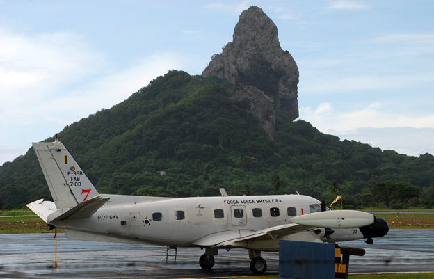 A small Brazilian Air Force radar plane prepares to leave an airport strip in front of a green, rocky, hill