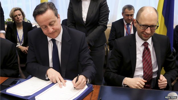 Britain's Prime Minister David Cameron sits next to Ukraine's Prime Minister Arseniy Yatsenyuk (R) during a signing ceremony at a European Union leaders summit in Brussels (March 21, 2014)