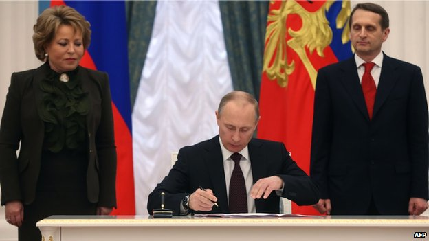 Vladimir Putin (C) signs a law on ratification of a treaty making Crimea part of Russia, during a ceremony in the Kremlin, with Valentina Matviyenko (L), the speaker of the upper house of Russian parliament, and Sergei Naryshkin (R), the speaker of parliaments lower house (21 Marc 2014)
