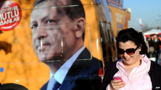 Woman uses her smartphone as she walks past a portrait of Turkish PM Recep Tayyip Erdogan (21 March 2014)