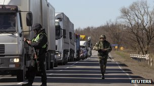 Ukrainian servicemen check trucks at a checkpoint in the Kherson region adjacent to Crimea