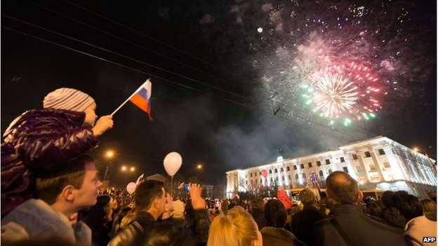 A young boy waves a Russian flag as people look at fireworks in the Crimean city of Simferopol (21 March 2014)