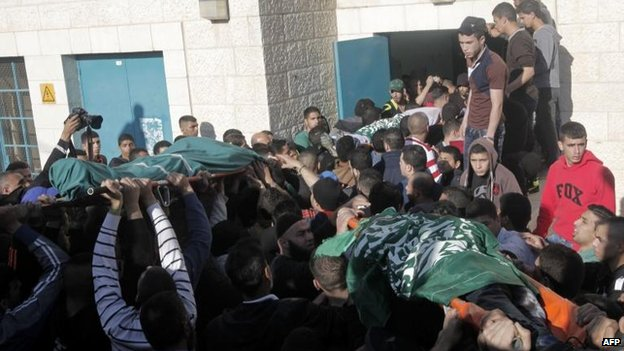 Palestinians carry the bodies of three men killed in the Israeli raid, 22 March