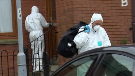 forensics officer leaving house with holdall