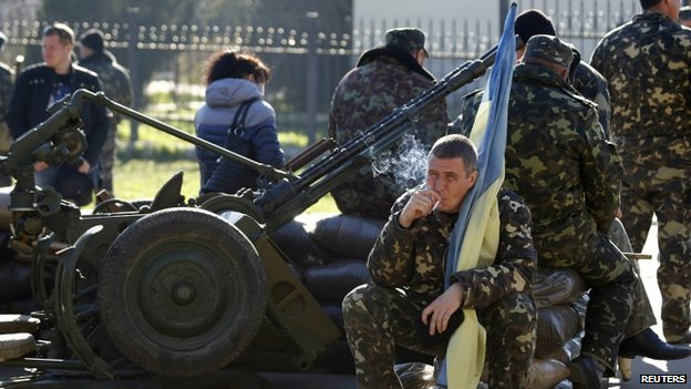 A Ukrainian serviceman holds a flag of Ukraine and smokes at Belbek base. Photo: 22 March 2014