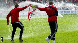 Aberdeen's Peter Pawlett and Jonny Hayes have to be on their toes to avoid the sprinklers pre-match