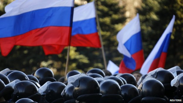 Russian flags are waved in front of Ukrainian riot policemen in central Donetsk