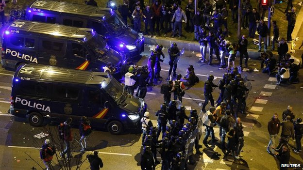 Riot police confront protesters after disturbances broke out at the end of the demonstration