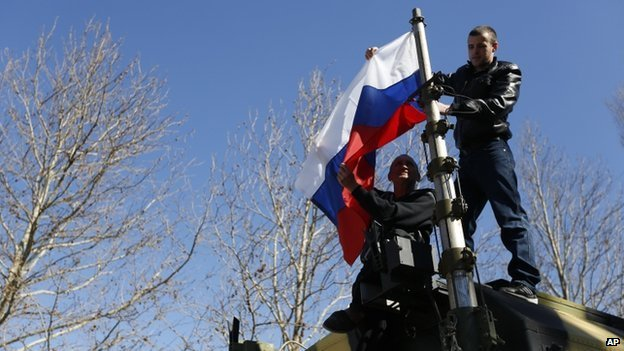 Two men hoist a Russian flag on a military vehicle after storming a base in Novofedorivka, Crimea