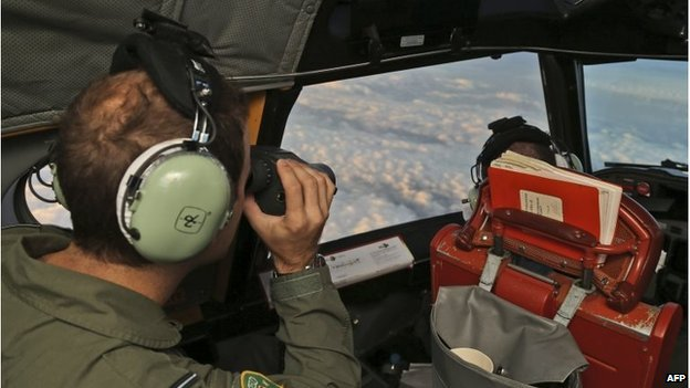 Crew members on board a Royal Australian Air Force AP-3C Orion scan for missing Malaysia Airlines flight MH370 in the southern Indian Ocean on March 22