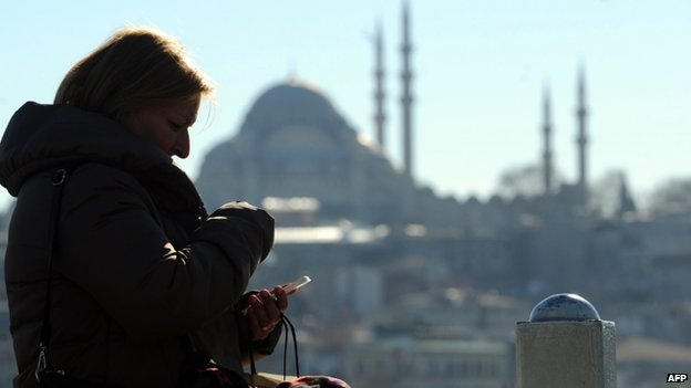 A Turkish woman looks at her smartphone in the Eminonu district of Istanbul