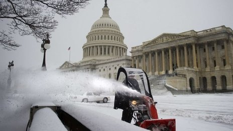 A maintenance man ploughs the sidewalk at the US Capitol in Washington