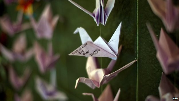 Origami cranes containing prayers and messages for those on board flight MH370 hanging from a wall at a shopping centre in Bangsar, Malaysia (23 March 2014)