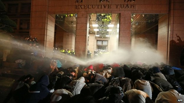 Protesters are sprayed with a water cannon during a demonstration outside the Executive Yuan in Taipei early on 24 March 2014