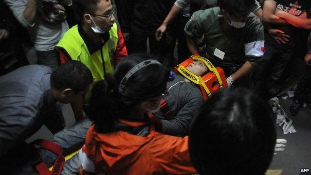 Paramedics carry an injured protester on a stretcher at the Executive Yuan in Taipei early on 24 March 2014