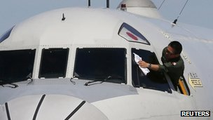 A Japan Maritime Self-Defence Force Lockheed P-3C Orion aircraft crew member wipes the windshield of the aircraft before it takes off from RAAF Base Pearce to search for the missing Malaysian Airlines Flight MH370, in Bullsbrook near Perth, 24 March 2014