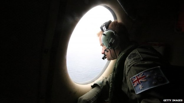 Aircrew look out of a window of a Royal Australian Air Force AP-3C Orion