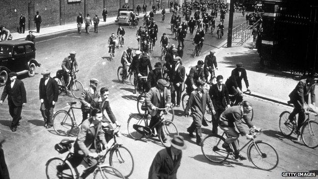 circa 1939: A general view of cyclists arriving for work at Chatham Dockyard