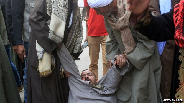 A relative of a supporter of Egyptian ousted Islamist president Mohamed Morsi is supported as he faints outside a courthouse