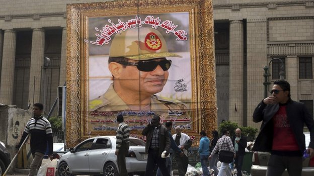 People walk past a huge portrait of Egypt's army chief, Field Marshal Abdel Fattah al-Sisi, in front of the High Court of Justice in central Cairo