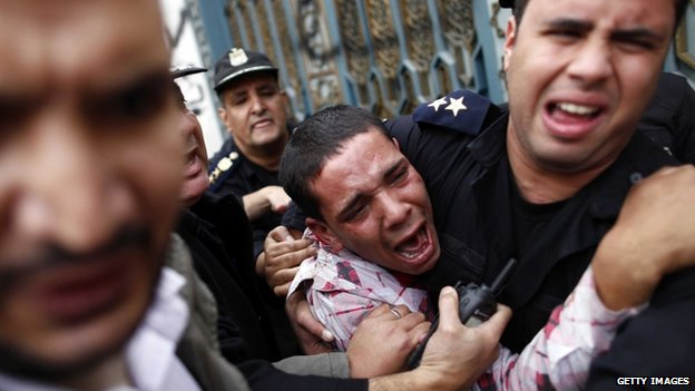 Policemen protect an opposition demonstrator after a scuffle with members of the Muslim Brotherhood