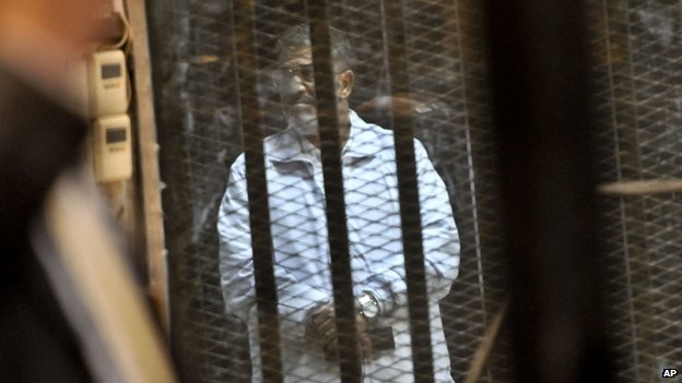 Mohammed Morsi stands inside a glassed-in defendant's cage