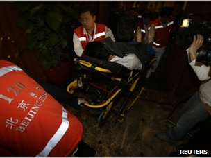 Medical personnel transport a family member of a passenger aboard Malaysia Airlines MH370 who collapsed after watching a television broadcast of a news conference, at the Lido hotel in Beijing on 24 March 2014