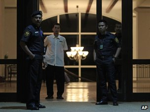 Malaysian auxiliary police officers stand guard at the entrance of a hotel where Chinese relatives of passengers aboard the missing Malaysia Airlines plane are staying, in Bangi, outside Kuala Lumpur, Malaysia, on 24 March 2014.