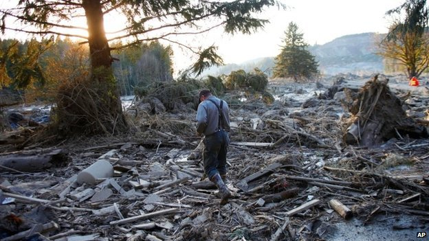 A man walks across the rubble on the east side of the mudslide near Oso, Washington, on 23 March 2014
