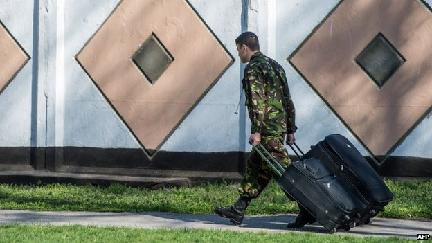 A Ukrainian marine carries his belongings as he leaves his military unit, Ukraine's only marine battalion, in the eastern Crimean port city of Feodosiya on 24 March 2014.
