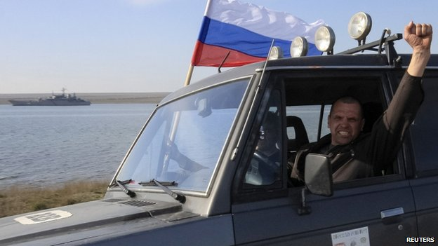 A member of a pro-Russian self defence unit gestures as he drives past the Ukrainian naval landing vessel Konstantin Olshansky in Donuzlav bay in Crimea on 24 March 2014