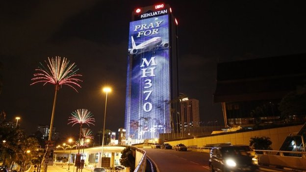 "An office building is illuminated with lights displaying ""Pray for MH370"" in Kuala Lumpur on 24 March 2014"
