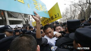 Family members of passengers onboard Malaysia Airlines Flight MH370 attempt to push past policemen during a protest, near Lido Hotel in Beijing, 25 March 2014