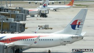 A ground staff member (bottom C) takes shade under a Malaysia Airlines plane at Kuala Lumpur International Airport (KLIA) in Sepang on 25 March 2014
