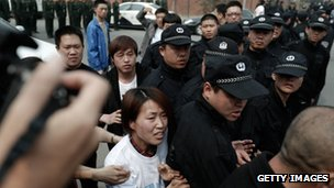A family member of a passenger from the missing Malaysia Airlines flight MH370 clashes with Chinese police outside the embassy in Malaysia on 25 March 2014 in Beijing, China