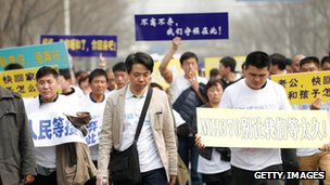Chinese relatives of flight MH370 walk towards the Malaysian Embassy on 25 March 2014 in Beijing, China