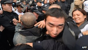 Grieving Chinese relatives of passengers on missing Malaysia Airlines flight MH370 try to remove a police barricade blocking journalists as they gather to protest outside the Malaysian embassy in Beijing on 25 March 2014