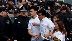 Grieving Chinese relatives of passengers on missing Malaysia Airlines flight MH370 walk past a police barricade as they gather to protest outside the Malaysian embassy in Beijing on 25 March 2014