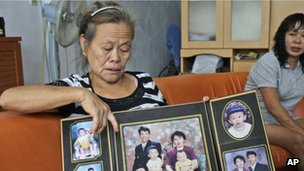 Suwarni the mother of Sugianto Lo, who was onboard the Malaysia Airlines plane MH370 with his wife Vinny, shows her son's family portraits at her residence in Medan, North Sumatra, Indonesia, Tuesday, 25 March 2014