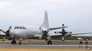 Ground crew watch as a Royal Australia Air Force AP-3C Orion runs its engines for maintenance during a no fly day in the search for missing Malaysia Airlines flight MH370 in Perth, Australia, 25 March  2014